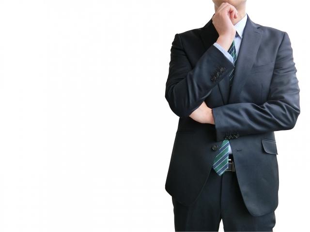 問題について考えるビジネスマン(東京オリンピックの問題点イメージ)