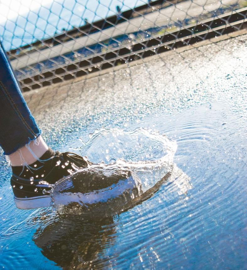 水たまりと靴 (雨の日の観光イメージ)